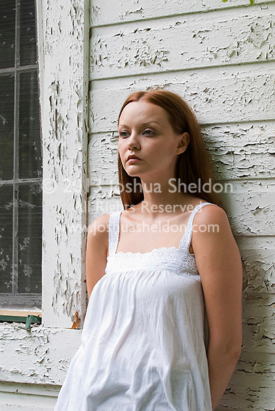 Young woman wearing a white dress leaning against a peeling white wall