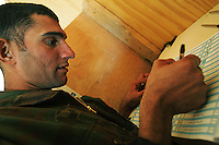 an iraqi soldier from 3d battalion, 1st brigade, 2nd Iraqi Army division makes his choice while voting in the Iraqi National elections at their base in Camp Ramadi at a poling site under the administration of the Indipendent Electoral Commision of Iraq on Mon Dec 12 2005. At the end of the day about 2000 soldiers will vote at this site according to An Iraqi official.