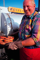 Portrait of smiling man making Texas-style barbecued ribs at a fair.