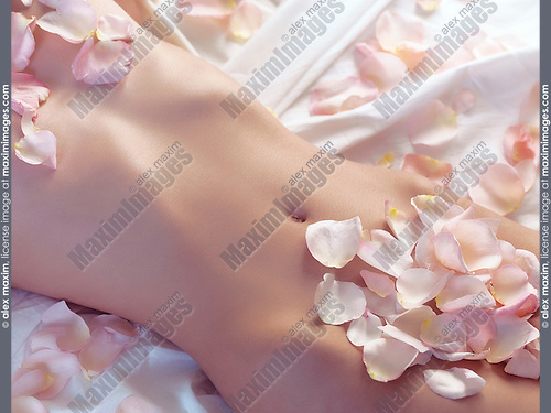 Young naked woman lying on bed with pink rose petals covering her body