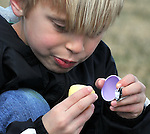 Dylan Lichtman, 6, of South Windsor, looks inside a plastic egg for a prize during the 41st Annual Imperial Oil Egg Hunt, Friday, April 6, 2012, at South Windsor High School. (Jim Michaud/Journal Inquirer)