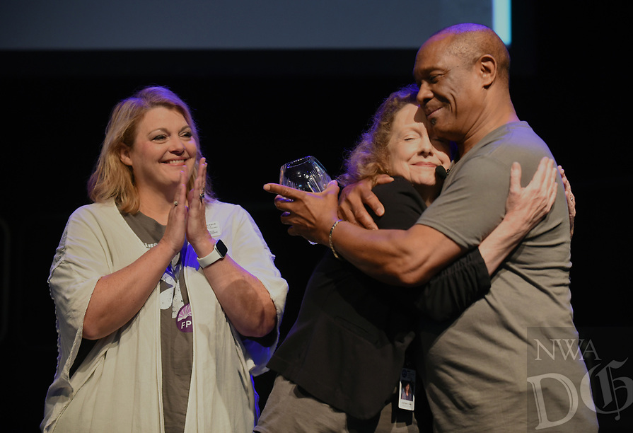 NWA Democrat-Gazette/DAVID GOTTSCHALK John L. Colbert (right), superintendent of Fayetteville Public Schools, hugs Kathleen Hale Wednesday, August 7, 2019, after she received the 2019 Triumph Award during the Fayetteville Public Schools annual Convocation ceremony in Bulldog Arena on the Fayetteville High School campus. The event, which features performances by students, informational presentations and awards, serves as a kickoff to the school year which begins Tuesday in Fayetteville.