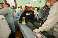 An injured press-photographer being treated during the violent protests across the country. Kiev. Ukraine. Feb. 18, 2014. (Photo by Msyslav Chernov / UnFrame)