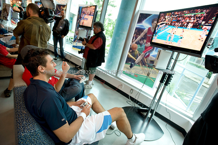 7/29/2008--Vancouver, BC, Canada..Andrea Bargani (Toronto Raptors) plays on the new NBA Live 2009 game at EA (Electronic Arts) World Wide Motion Capture Facility in Vancouver, British Columbia, Canada. EA is an American developer, marketer, publisher, and distributor of computer and video games...The NBA players wear custom fit motion capture suit and have reflective balls, called ?markers? (not sensors), attached to the suit with Velcro. The markers are made of rubber and are covered with reflective tape...Each camera has its own light source, the red ring around each camera ? the lens is the dark spot in the centre. The red light shines into the shoot area, hits the marker and reflects the light back to the camera. The camera records that point of light as a dot on the screen. The software identifies each dot and mocap staff take those dots and attach them to the character provided by the game team. The ?bones? of the game character are pulled around by the dots in the same manner a string would pull a marionette?s body around...A typical team will shoot 8-10 days of motion capture each year and capture about 20,000 seconds (5.5 hours) of animation. The animators on the game team can then manipulate the data as they see fit and deliver it to the software engineers to put into the game...©2008 Stuart Isett. All rights reserved.