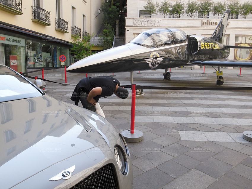"Switzerland. Canton Ticino. Lugano. A young man bends over and looks at a Breitling plane in Via Nassa and Piazzetta San Sarlo. Bentley badge on a car. The most deluxe and expensives shops are located in the street ""Via Nassa"". 17.04.2011 © 2011 Didier Ruef"