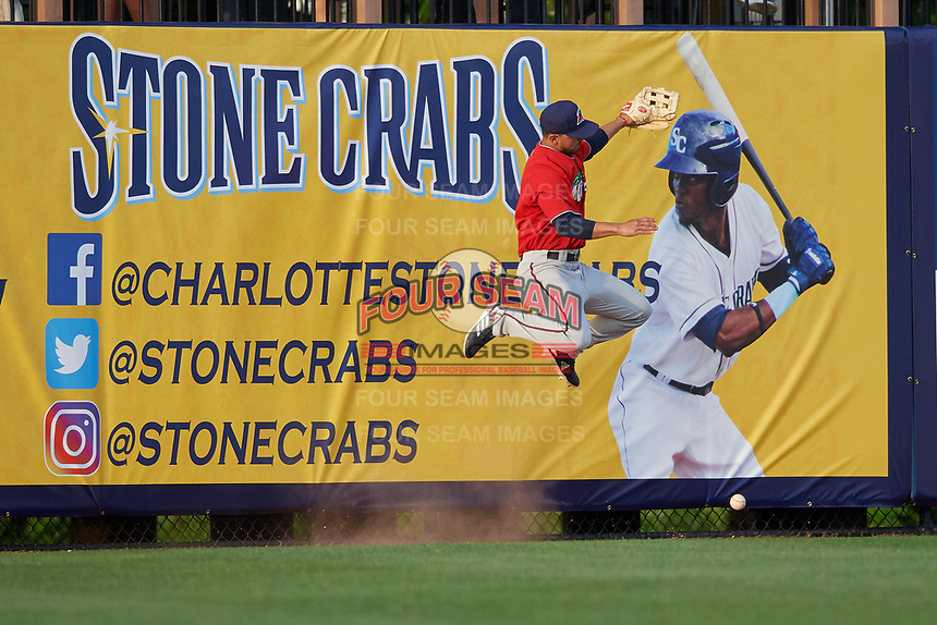 Fort Myers Miracle left fielder Mark Contreras (5) attempts to catch a fly ball at the wall during a Florida State League game against the Charlotte Stone Crabs on April 6, 2019 at Charlotte Sports Park in Port Charlotte, Florida.  Fort Myers defeated Charlotte 7-4.  (Mike Janes/Four Seam Images)