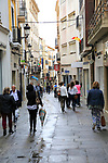 People shopping wet day pedestrianised street, Caceres, Extremadura, Spain