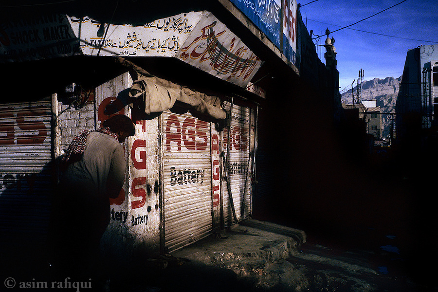 Storefront during an anti-government business strike in the city of Quetta - a view of the Chiltan mountain range in the background