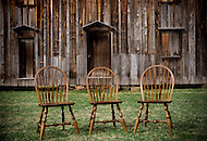 Three chairs sit outside of an old barn at the Stagville Plantation in Durham, North Carolina