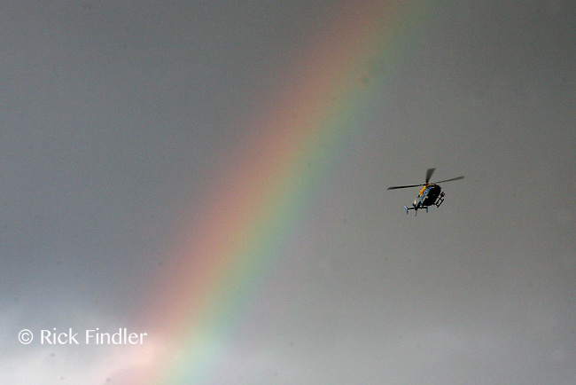 PH: Rick Findler..08.08.11 A police helicopter flies in front of a rainbow as youths and police clash in Hackney today as riots spread across the whole of London including Croydon and Clapham.