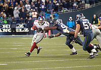 27 Nov 2005:   New York Giants running back Tiki Barber tries to break free from Seattle Seahawks defensive end Bryan Fisher at Quest Field in Seattle, WA.