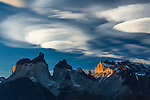 Sunset light illuminates the yellow granite face of Monte Almirante Nieto.    At left are the Curenos del Paine, with Monte Almirante Nieto on the right.  Between the Cuernos and Monte Almirante Nieto are the tips of Torre Sur and Torre Central.  Lenticular clouds are forming over the peaks.  Torres del Paine National Park in Patagonia, Chile.  A UNESCO World Biosphere Reserve.  A polarizing filter was used to cut haze, increasing the contrast.