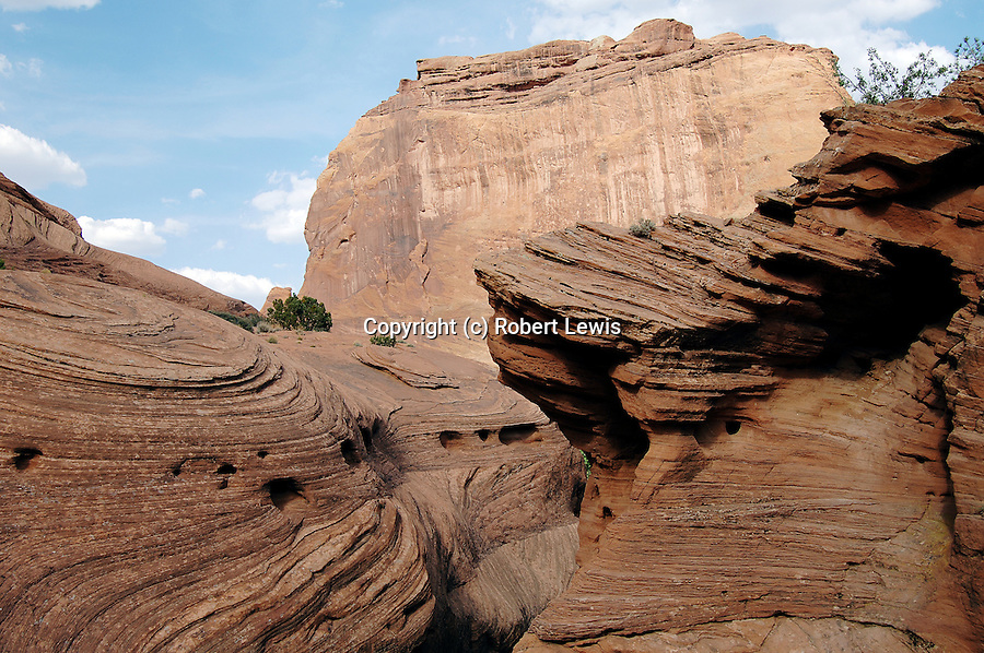 the curved patterns resembling comet like orbits contrast the sheer faces of the opposite cliffs.