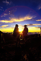 Two people with sunrise between them on Haleakala at the House of the Sun