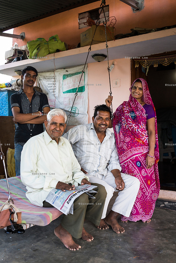 (L-R) Nitin Jat, 20, Chetan Jat, 42, Bhagirata Jat, 72, and Lalita Jat, 40, pose for a family portrait in their home in Maheshwar, Khargone, Madhya Pradesh, India on 13 November 2014. Nitin, wants to continue doing Fairtrade cotton farming like the generations before him, but would like to also have a government job in the village so he can have an added source of income and pension (as did his grandfather). Photo by Suzanne Lee for Fairtrade