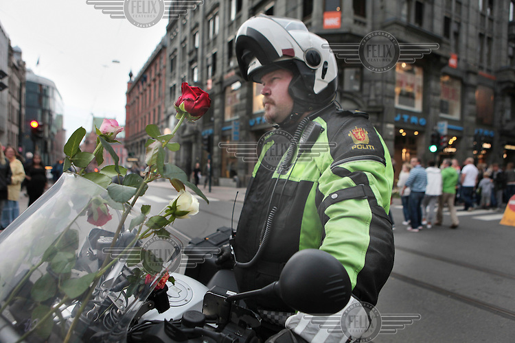A policeman holds flowers on his bike in central Oslo on the day that Anders Behring Breivik made his first court appearance following his arrest for two terrorist attacks on 22nd July 2011. A large vehicle bomb was detonated near the offices of Norwegian Prime Minister Jens Stoltenberg resulting in several injuries and deaths and a mass shooting attack claimed dozens of lives on Otoeya Island about 40 Kilometres from Oslo. Breivik confessed to carrying out both atrocities.