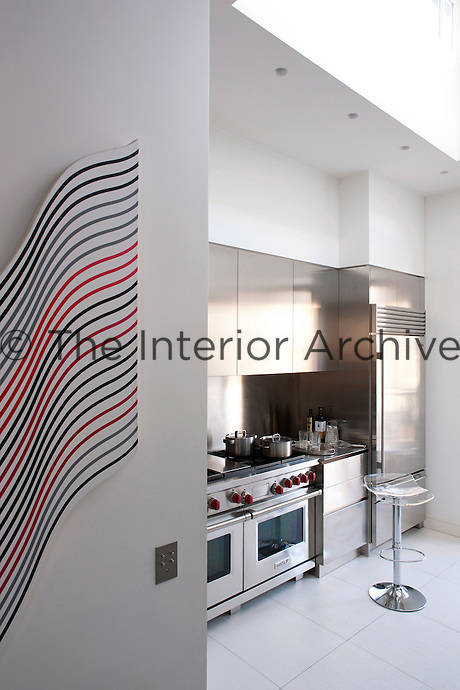 The contemporary stainless steel kitchen is by Boffi on a polished sandstone floor
