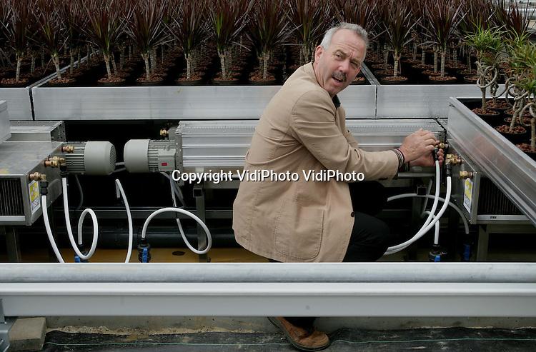 Foto: VidiPhoto..BEMMEL - Stef Huisman in zijn nieuwe kas tussen de planten. Op de achtergrond een warmtewisselaar. Huisman bezig de eerste energieleverende kas van Nederland. De zonnewarmte wordt opgevangen en omgezet in energie.