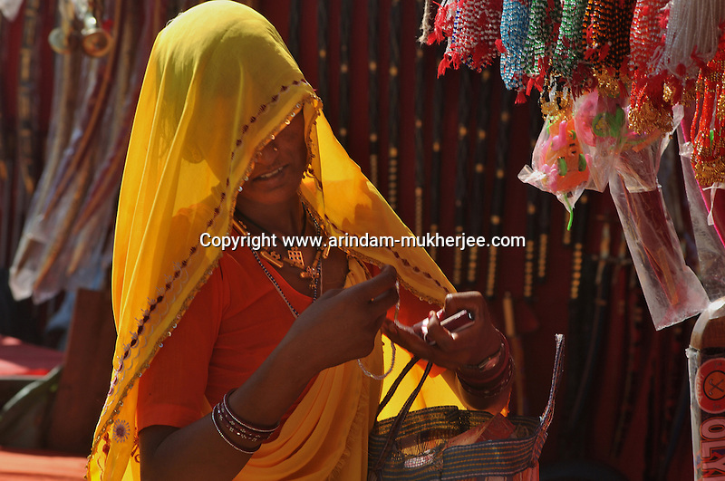 """A rajasthani lady buying ornaments from the annual Pushkar fair.  Pushkar during its famous Camel Fair gives a rare glimpse of earthy village life with a heady mix of colours, faith and frenzy - things that define """"Indianness"""" to a tourist's eyes. The town nestled at the foothills of the rugged Aravalli in Rajasthan, owes its raison d'être to the sacred Pushkar lake surrounded by more than 500 Hindu shrines. This November, begins the camel (and horse) fair - one of the biggest animal fairs on earth. Though chiefly a secular occasion, like most of the Indian fairs Pushkar fair too merges with a Hindu rite of bathing on the full-moon day. It's a visitor's delight to watch waves after waves of colourfully clad people arriving for holy dips in the lake. During this fortnight long festival, Pushkar becomes a temporary home for holy men, con men, devotees, salesmen - in brief, all kinds of men and women. The camel trading yard spreads across the desert-stretch fringing the little town. It shelters some 50,000 camels and their brightly turbaned owners/buyers from all over Rajasthan. While the desert comes alive with the performances of tribal musicians and dancers, the animal traders negotiate deals with the buyers; or roll out bread for lunch. The bleating of camels, hurtling of scruffy boys to get a share of animal dung - create an ambience of unadulterated simplicity. Arindam Mukherjee"""