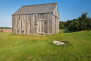 Wagon wheel keeps the doors of a barn closed at the Morrison House in Londonderry, New Hampshire USA which is part of scenic New England.