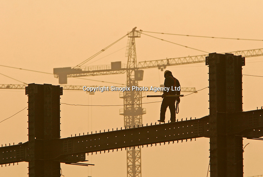 A construction worker walks on a steel beam high in the air at the construction site of the Olympic aquatic center in Beijing, China. China's state auditors will extend their search for government corruption next year to the 2008 Beijing Olympics as billions are spent to construct massive Olympic venues..