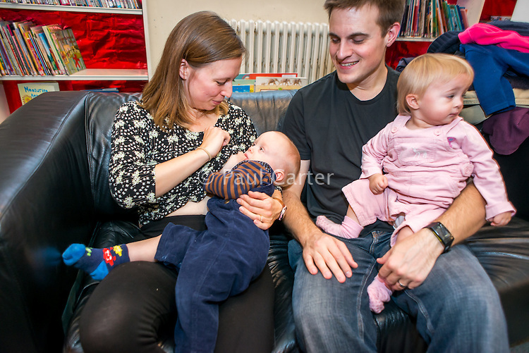 A young woman breastfeeds one her twins while sitting on a sofa in a public library. Her other twin sits next to her on her husband's lap.<br /> <br /> 24/11/12<br /> Hampshire, England, UK