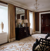 Full-length curtains and dark antique furniture create a feelling of opulence in this hallway