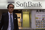 May 10, 2016, Tokyo, Japan - A businessman walks by a SoftBank shop in downtown Tokyo, Japan on May 10, 2016. SoftBank Group Corp. reported a drop in operating profit to 124 billion yen and a net profit of 45 billion yen. (Photo by AFLO)