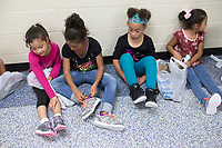NWA Democrat-Gazette/CHARLIE KAIJO A group of girls admire their new shoes at Grace Hill Elementary School in Rogers, AR on Friday, September 7, 2017. Elementary School students received a special gift, organized by Walmart associates and Samaritan's Feet. Each student received a new pair of shoes for the new year.