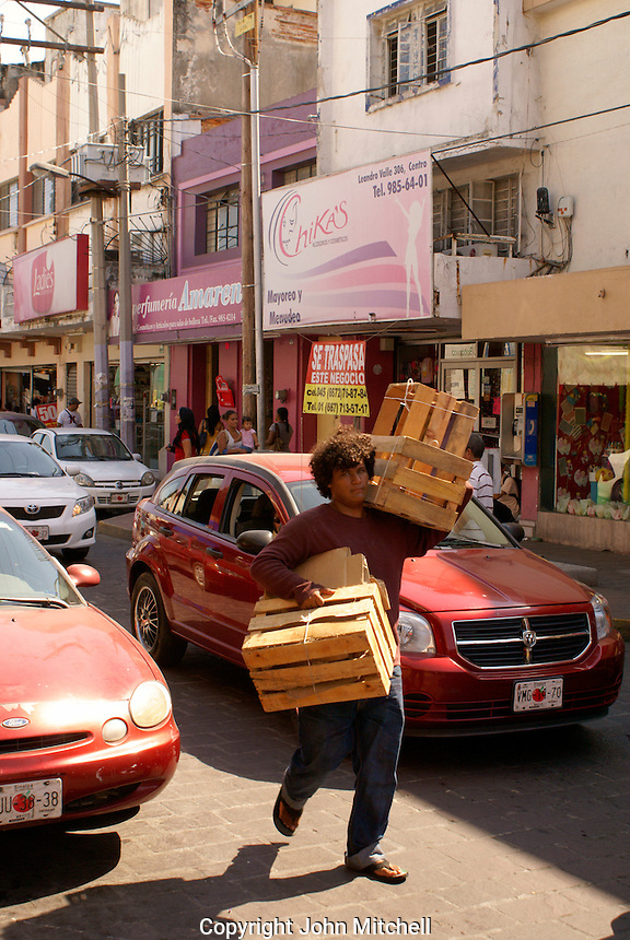 Man carrying wooden boxes through a crowded downtown street, Mazatlan, Sinaloa, Mexico