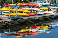 Colorful kayaks on a rack and their reflections in the West Basin of Mamaroneck Harbor in Harbor Island Park located in Mamaroneck, New York.