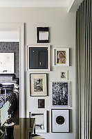 A collection of artworks is displayed in one corner of the sitting room. A door leads through to the bedroom.