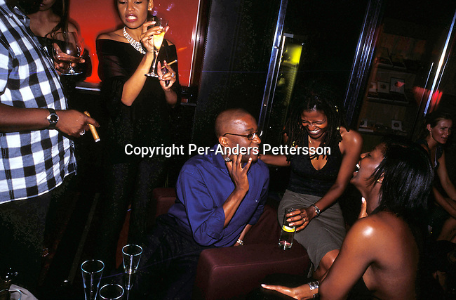 dippnig00162 People Nightlife JOHANNESBURG, SOUTH AFRICA -  MAY 5 Unidentified up market black people drinking champagne and smoking cigars in the champagne bar at Kilimanjaro, an up market club, on May 5, 2003 in Melrose Arch, a suburb in Johannesburg, South Africa. A growing number of people belong to the new black elite in the country. Well educated and connected, they have risen from the poverty in the townships to a very different lifestyle, since the fall of Apartheid and the start of democracy in the country in 1994. .©Per-Anders Pettersson/iAfrika Photos..