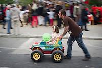 **Hinweis: Dieses Bild ist Teil der Fotostrecke 1.Mai** Berlin, Ein Mann schiebt ein Kind am Mittwoch (01.05.13) in Kreuzberg in Berlin, waehrend des Myfestes, in einem Spielzeugauto. Foto: Timur Emek/CommonLens