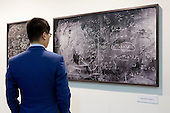 27 February 2014, London, United Kingdom. Pictured: A man studys a blackboard covered in formulae by Alejandro Guijarro. The Art14 Art Fair at Olympia Grand Hall, London, opens its doors to the public from 28 February to 2 March 2014. Art14 London features 180 galleries from 40 countries with works from emerging talents to modern masters.