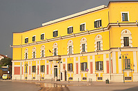 National administrative buildings in bright yellow and red in classic architecture style around the square. The Tirana Main Central Square, Skanderbeg Skanderburg Square. National Tourist Organisation. Tirana capital. Albania, Balkan, Europe.