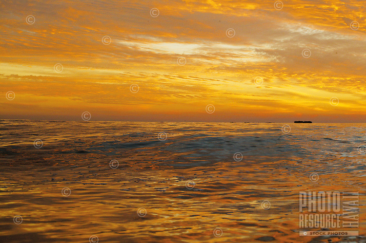 gentle ocean waves under tropical clouds of orange and yellow at sunset