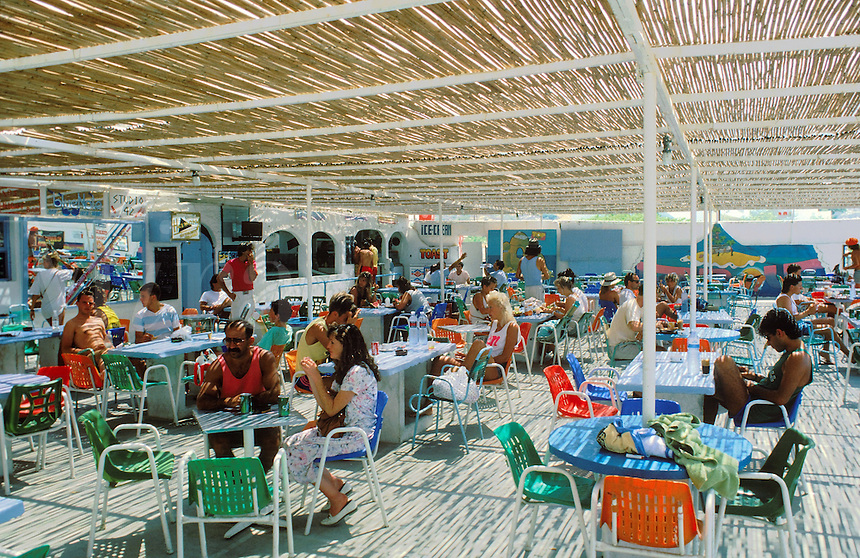 Tourists fill the tables at an outdoor restaurant near the ferry port at Ios.