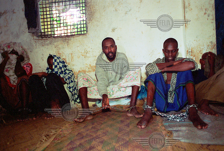 photo: Sven Torfinn.Somalia, Mogadishu, july 2000.Prison and prisoners of Sharia court in Mogadishu. Some of the prisoners are brought there by their parents for rehabilitation, other where arrested by the militia .of the court after committing a criminal offence. Man is showing the chain between his feed.