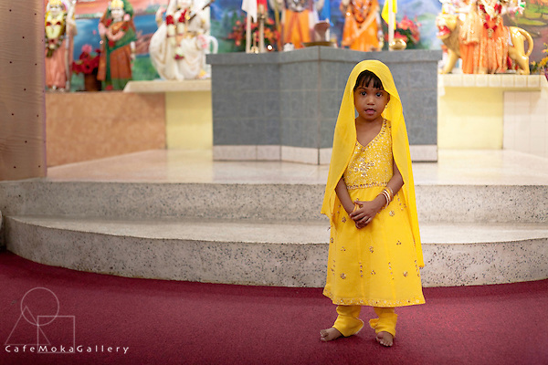Young girl in yellow ina Hindu temple in Felicity, Divali,Hindu festival of light,