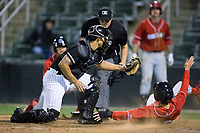Mickey Moniak (22) of the Lakewood BlueClaws slides across home plate under the tag of Kannapolis Intimidators catcher Seby Zavala (21) as home plate umpire Mike Rains looks on at Kannapolis Intimidators Stadium on April 6, 2017 in Kannapolis, North Carolina.  The BlueClaws defeated the Intimidators 7-5.  (Brian Westerholt/Four Seam Images)