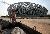 "A construction worker mixes cement in front of the National Stadium, AKA ""The Bird's Nest"" in Beijing, China..04 Sep 2007"
