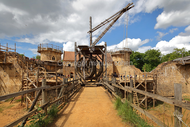 Lifting gear or squirrel cage with double drum, in front of the Chapel Tower (left), North Range or Logis Seigneurial and Great Tower or Tour Maitresse (right), seen across a footbridge over the moat trench, at the Chateau de Guedelon, a castle built since 1997 using only medieval materials and processes, photographed in 2017, in Treigny, Yonne, Burgundy, France. The Guedelon project was begun in 1997 by Michel Guyot, owner of the nearby Chateau de Saint-Fargeau, with architect Jacques Moulin. It is an educational and scientific project with the aim of understanding medieval building techniques and the chateau should be completed in the 2020s. Picture by Manuel Cohen