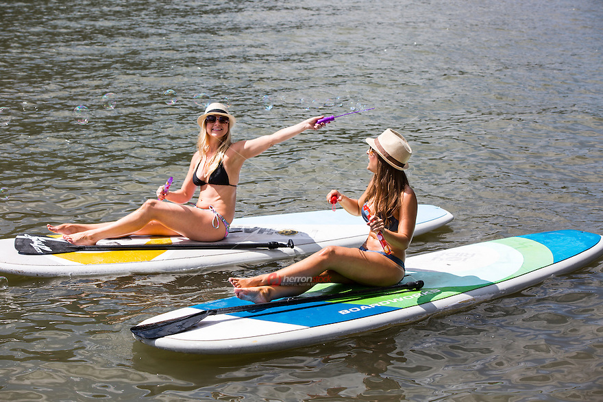 Two young attractive sexy females on stand up paddle board, SUP, blowing bubbles on Lake Travis, beat the blistering 100 degree plus summer heat in Austin, Texas.