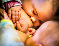 "Close-up of 5 month old twins brestfeeding at the same time.<br /> <br /> Image from the ""We Do It In Public"" documentary photography project collection: <br />  www.breastfeedinginpublic.co.uk<br /> <br /> Hampshire, England, UK<br /> 11/02/2013"