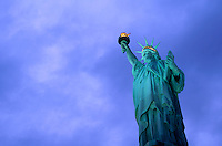 AVAILABLE FROM JEFF AS A FINE ART PRINT.<br /> <br /> AVAILABLE FROM JEFF FOR COMMERCIAL AND EDITORIAL LICENSING.<br /> <br /> The Statue of Liberty Illuminated at Dusk with Dramatic, Cloudy Blue Sky.<br /> <br /> Liberty Island, Upper New York Bay, New York City, New York State, USA