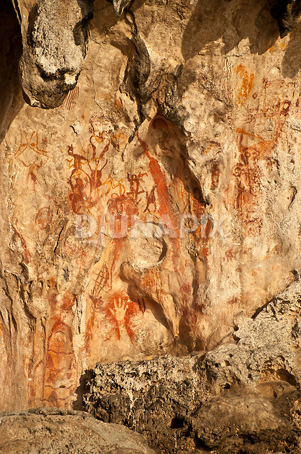 Prehistoric rock art on a cliff face near Mai Mai village, Namatota Strait, near Kaimana, Papua. One of the paintings resembles a fishing net.