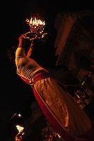 Hindu priest conducting the evening worship service at dusk with arti (108 ritual lamps) and bhajan (hymns) at the Bagmati river, Pashupatinath, Nepal