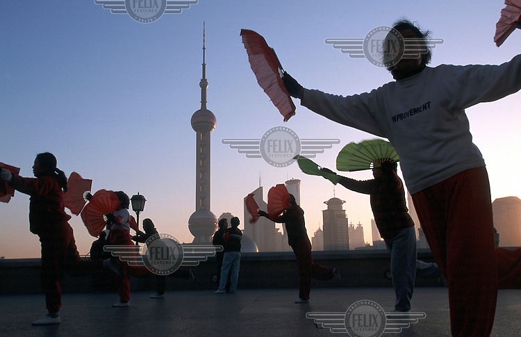 A group of residents practice Tai chi. The Bund is one of the favourite morning exercise spots for Shanghai's early risers, partly due to its spectacular view of the Pudong Financial District just across the Huangppu River.