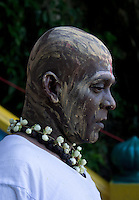 tamile Hindu with shaved head and  body-painting, sacrifices to  to support salvation of ancestors among other rituals at Thaipusam ceremonies,  Batu Caves, Kuala Lumpur, Malaysia, 2012. Thaipusam ceremonies, celebrated by tamile Hindu community in Malaysia, take place  in Sanctuary of Batu Caves at the border of Kuala Lumpur, each year around end of January or beginning of February, according to Hindu moon calendar. The event is paying hommage to Lord Murugan, a spirit or god created by Shiva to lead the army of gods against the army of evil demons, finally defeating the evil spirits. There are many ways to present offerings or sacrifices for this major religious event. Devotees mortify their bodies by carrying heavy kavaris with spears fixed in their skin or fruits, flowers and little post with holy milk fixed with hooks in their skin, ascending the stairways to the sanctuary in trance, `followed by assistant  taking care and musicians playing loud and fast rhythmic trance music.  Many families shave their head in a ritual before ascending the stairways, as part of rituals to obtain salvation for their ancestors.